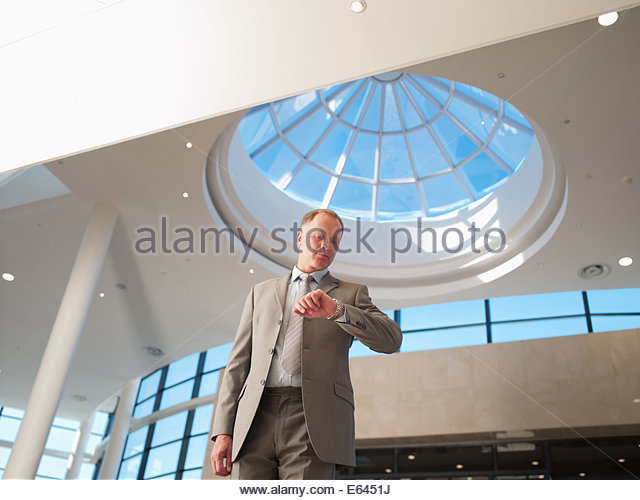 Businessman checking wristwatch - Stock Image