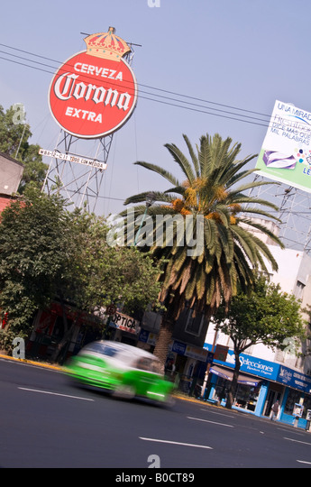 Iconic green VW Beetle used as a taxi in Mexico City. The Corona sign in the background is for Spanish beer. - Stock Image