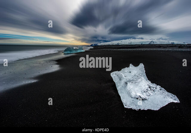 Icebergs washed upon the black sands of the Atlantic coast in southern iceland - Stock Image