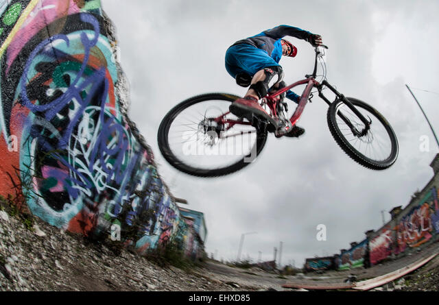 Mountain biker stunts on road, Bavaria, Germany - Stock-Bilder