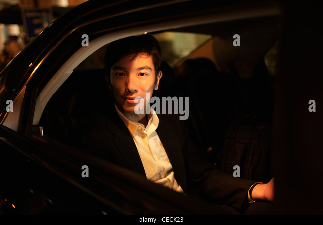 Young man sitting in car looking out of window at night - Stock Image