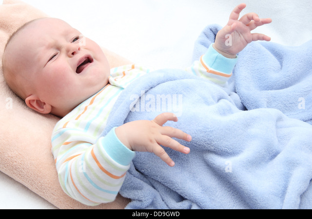little baby crying in bed - Stock Image