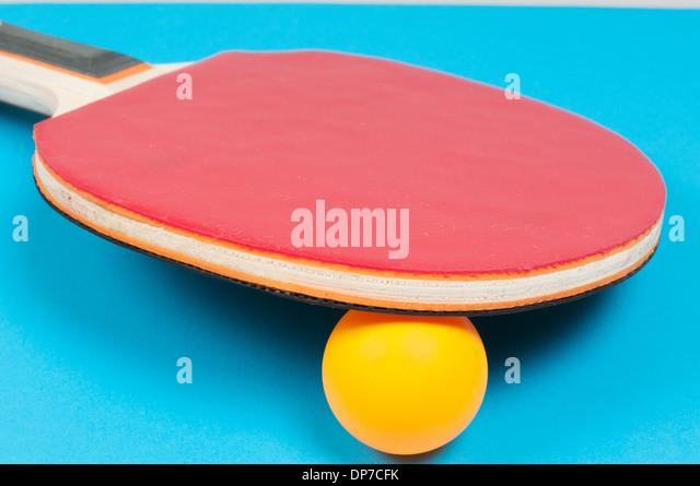 Table tennis racket with orange ball- stock image - Stock Image