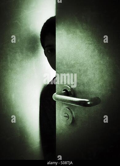 Scared boy hiding behind door - Stock Image
