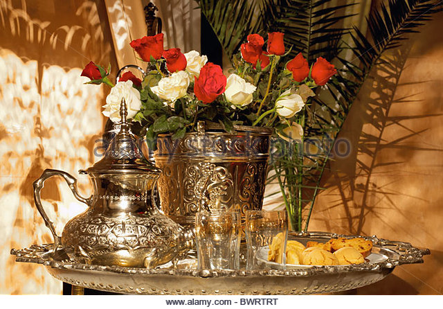 Festive decoration of a moroccan tea set with pasteries and roses - Stock Image