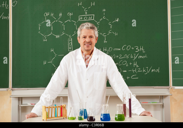 Germany, Emmering, Mature man standing in chemistry lab, smiling, portrait - Stock Image