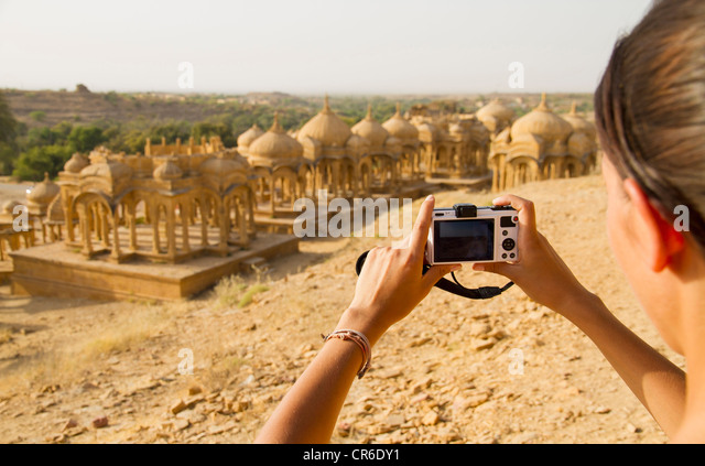India, Rajasthan,Jaisalmer, Female tourist photographing at Bada Bagh Cenotaphs - Stock-Bilder