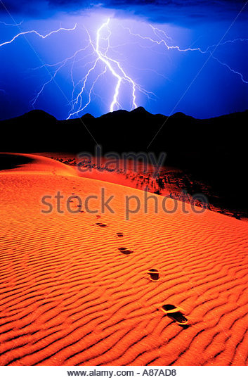 Footprints in sand dunes leading on pathway into the distance with  lightning in sky - Stock Image