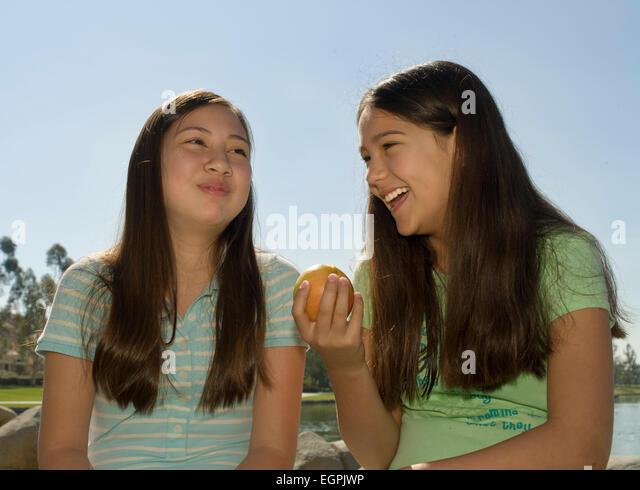 Vietnamese/Caucasian and Hispanic/Caucasian girlfriends laugh. MR  © Myrleen Pearson - Stock-Bilder