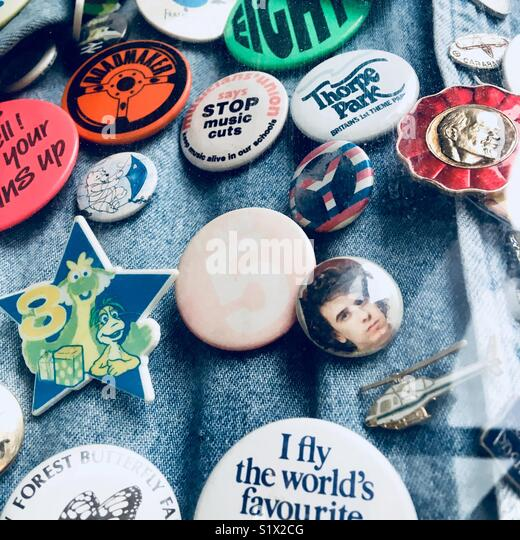 Eightie's badges pinned to a denim jacket. - Stock Image