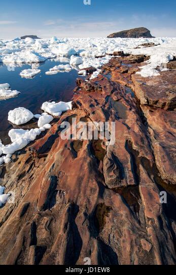Rocky coastline and sea ice landscape in Maberly, near Elliston on Cape Bonavista, Newfoundland, Canada - Stock Image