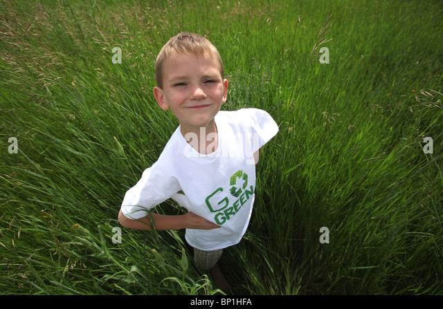 boy standing in tall green grass wearing 'go green' tee shirt - Stock-Bilder