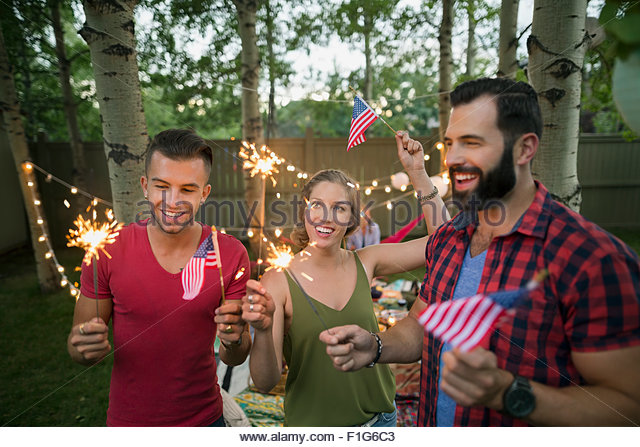 Friends sparklers American flags 4th of July party - Stock Image