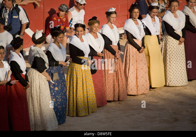 A row of women standing in the Arena dressed in Arlésienne costume before a bullfight, Arles, France - Stock Image