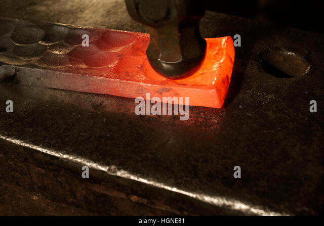 Glowing metal artworks will be completed in the smithy - Stock Image