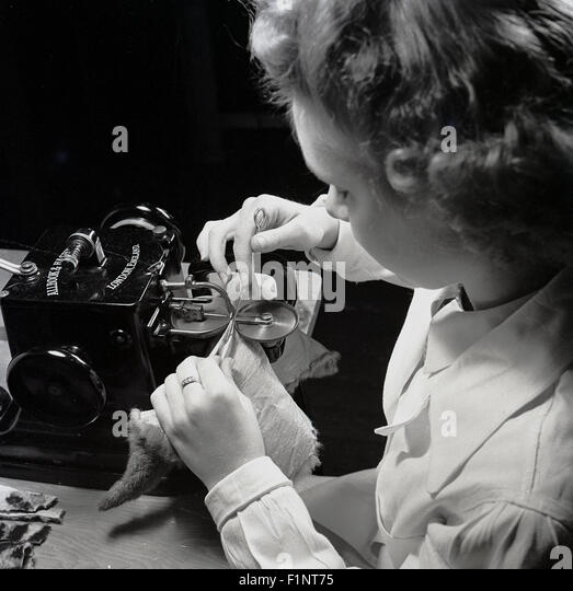 Historical, 1950s, female using a stitching or sewing machine to stitch a piece of fabric. - Stock Image