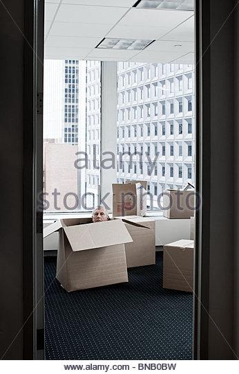 Businessman hiding in cardboard box - Stock Image