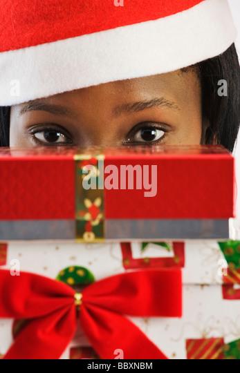 African woman wearing Santa suit peeking over Christmas gifts - Stock-Bilder