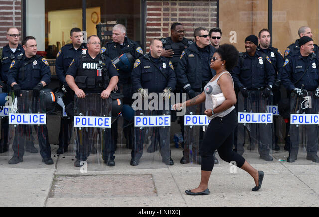 Baltimore, USA. 1st May, 2015. A womon walks by riots policemen in west Baltimore, Maryland, the United States, - Stock Image