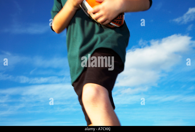 boy with rugby ball running - Stock Image