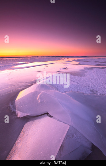 A frozen lake glows in morning twilight - Stock Image