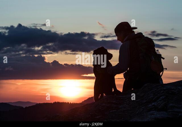 Hiker with dog at sunset on Art Loeb Trail near Black Balsam Knob - Blue Ridge Parkway, North Carolina, USA - Stock Image