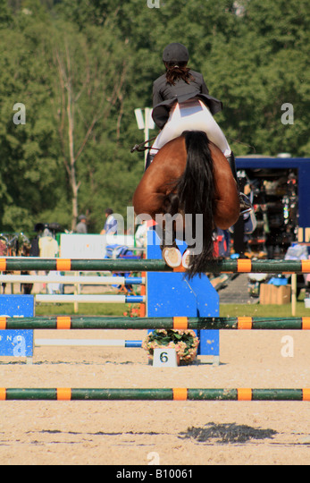 an unidentified rider jumps the first of a triple gate in an international junior s competition in Prague - Stock Image