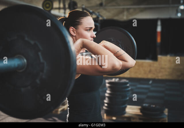 Fit young woman lifting barbells looking focused, working out in a gym - Stock Image