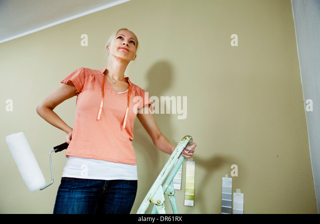 Woman painting an apartment, Munich, Bavaria, Germany - Stock Image