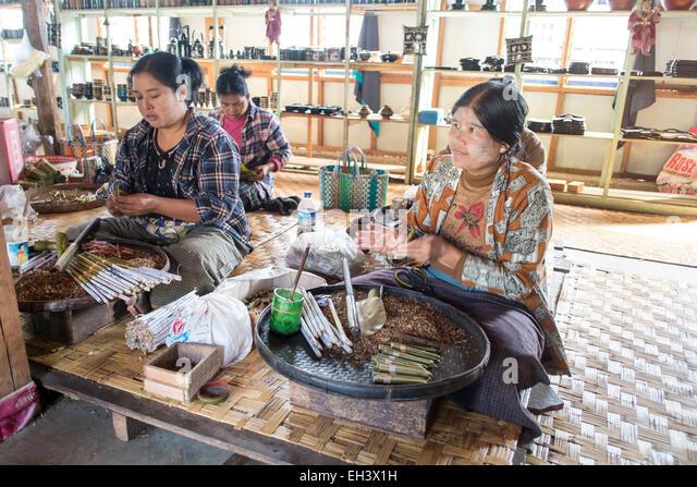 Women roll cigars in a hut on Inle Lake , Myanmar - Stock-Bilder
