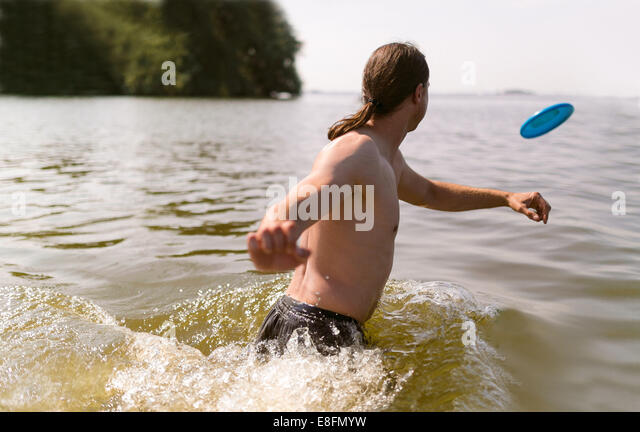 The Netherlands, Jsselmeer, Man in lake playing with plastic flying disc - Stock Image