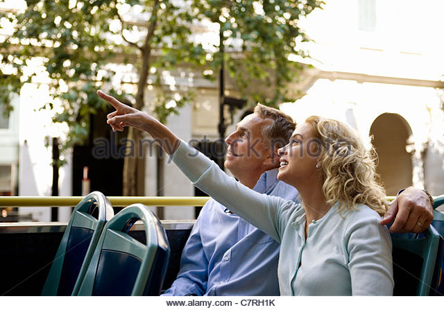 A middle-aged couple sitting on a sightseeing bus, admiring the view - Stock Image