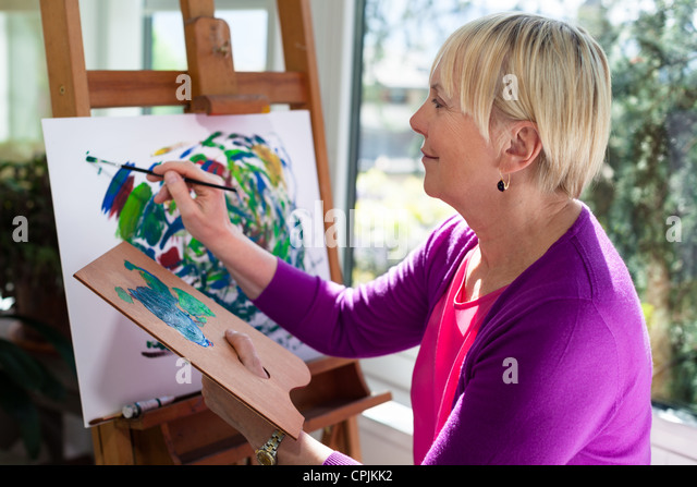 Happy retired woman painting on canvas for fun at home - Stock Image