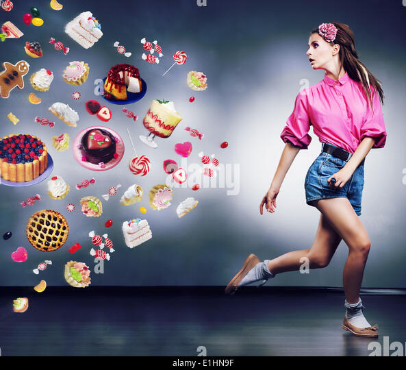 Escape. Resolute running woman refuses to eating tasty cakes and chocolate. Diet concept - Stock Image
