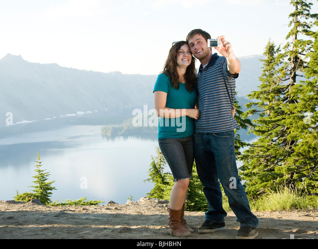 young couple taking a picture of themselves in front of a scenic view overlooking a beautiful lake - Stock-Bilder