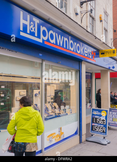 Woman looking in the window of H&T Pawnbrokers in Nottingham at pawned jewelry. - Stock Image