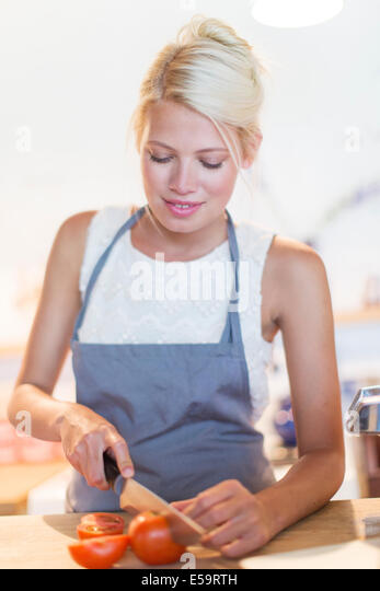 Woman slicing vegetables in kitchen - Stock Image