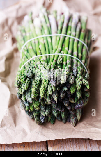 Fresh asparagus bunch on paper - Stock Image