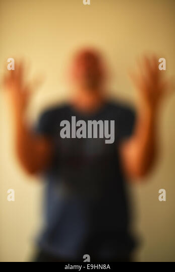 A man blurred looking angry and animated - Stock Image