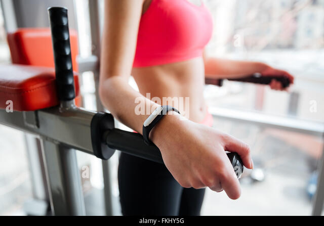 Attractive young woman athlete with fitness tracker on hand working out in gym - Stock-Bilder