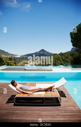 Woman sunbathing at poolside - Stock Image