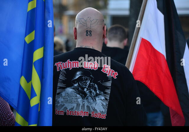 A participant wears a sweater that reads 'Glory and honour to the German soldier' and a neck tattoo that - Stock-Bilder