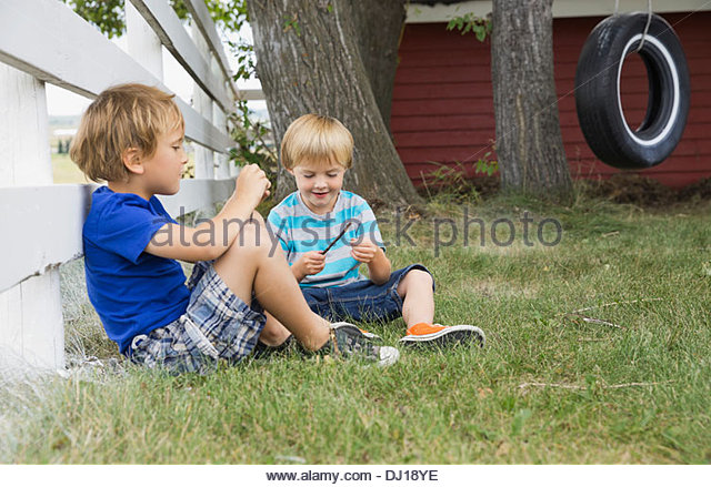 Young boys relaxing in back yard - Stock Image