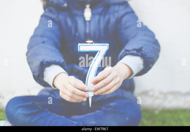 Girl sitting cross legged holding a number seven candle - Stock Image