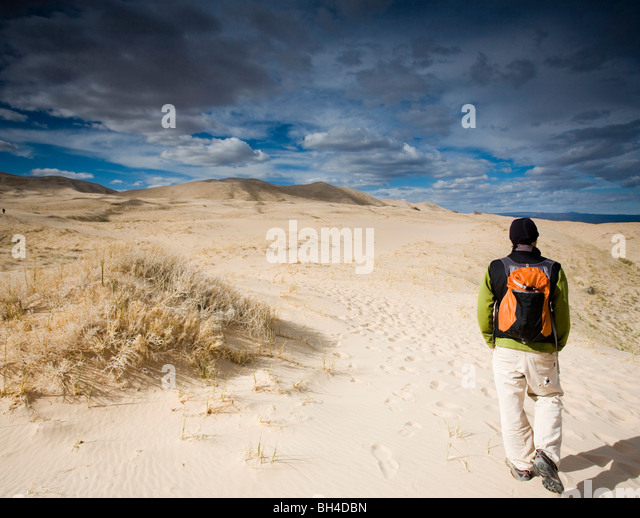 A man walks on natural sand dunes beneath a cloudy sky in Mojave Desert, California. - Stock Image
