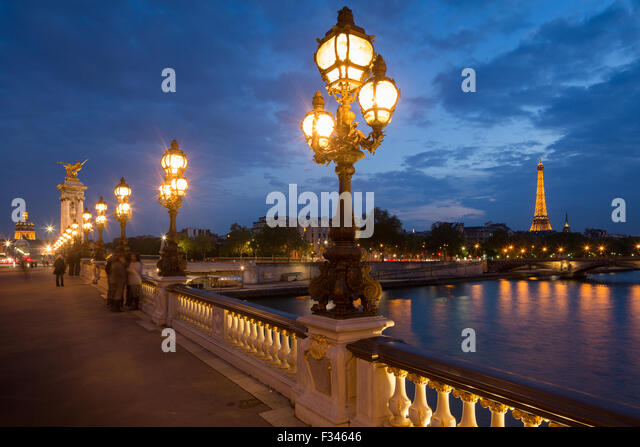 Pont Alexandre III, looking toward the Eiffel Tower over the River Seine at dusk, Paris, France - Stock Image