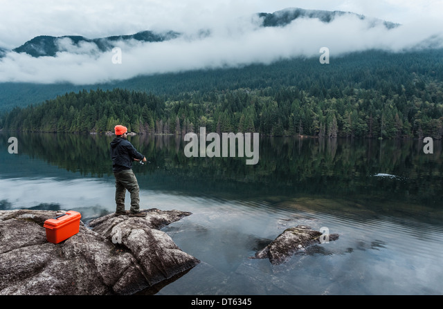 Man fishing from rocks, Buntzen Lake, British Columbia, Canada - Stock Image