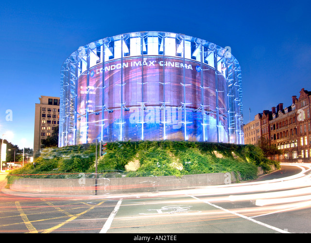 London's IMAX cinema and light trails from passing traffic at dusk. - Stock Image
