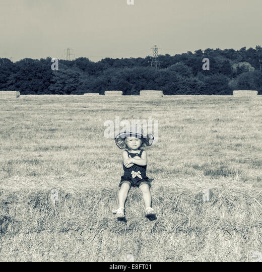 Girl sitting on hay bale with folded arms - Stock Image