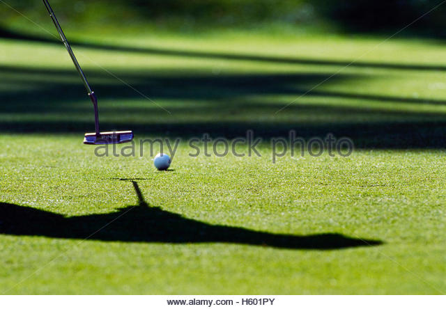 Golfer putting amongst shadows. - Stock Image